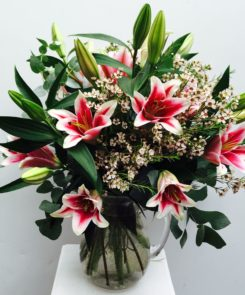 Pink Oriental Lilies with Waxflower & Eucalyptus in a glass jug